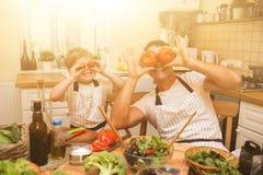烹调在有小儿子的厨房的厨师人 免版税库存照片