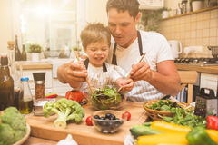 烹调在有小儿子的厨房的厨师人 库存照片