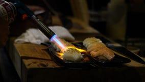 烹调在有小型发焰装置的日本料理店的人做的寿司变成焦糖 影视素材