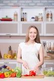 烹调在有成份的厨房里的妇女 免版税库存照片