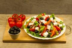烹调在木背景的夏天希腊沙拉 免版税库存图片