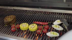 烹调在格栅的未被认出的厨师菜在餐馆厨房特写镜头 肉,玉米,西红柿 股票录像