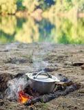 烹调在火在野餐,食物在木头,在河反映的树的水壶准备了,健康素食食物 免版税库存图片