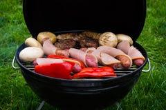 烹调在热的煤炭的一串烤肉的大角度观点的多汁牛排、汉堡、香肠和菜在一绿色草坪outd 库存图片