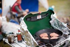 烹调在煤气喷燃器的绞细牛肉小馅饼 免版税库存图片