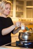 烹调在煤气炉的主妇膳食增加成份到煮沸的平底锅 免版税图库摄影
