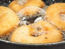 烹调在煮沸的油的油炸圈饼特写镜头  免版税库存图片