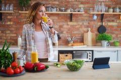 烹调在现代厨房的快乐的妇女 库存图片
