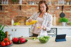 烹调在现代厨房的快乐的妇女 免版税库存图片