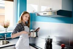 烹调在现代厨房里的美丽的白肤金发的妇女 免版税库存照片