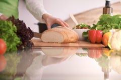 烹调在玻璃桌上的厨房里的人的手特写镜头与切面包的反射主妇 免版税图库摄影