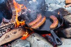 烹调在生铁长柄浅锅的香肠在营火,当野营时 好和正面营火食物 免版税库存照片