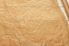 烹调在白色木桌上的Crumpled羊皮纸板料 免版税图库摄影