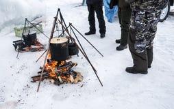 烹调在篝火的游人食物,烹调在雪在冬天 早餐、午餐和晚餐的准备食物 免版税图库摄影