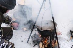 烹调在篝火的游人食物,烹调在雪在冬天 早餐、午餐和晚餐的准备食物 免版税库存图片