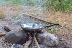 烹调在野外条件,煮沸的平底锅在营火 库存图片