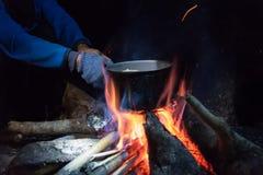 烹调在野外条件,煮沸的罐在picn的营火 免版税库存照片