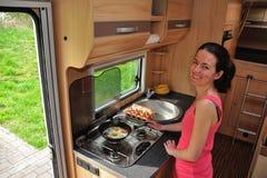 烹调在野营车的妇女 免版税库存图片