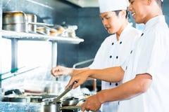 烹调在餐馆的亚裔厨师 库存照片