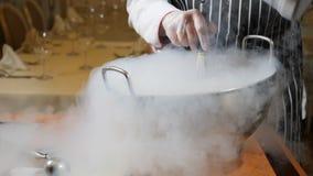 烹调在餐馆 烹饪器材在工作 手套的Proffessional厨师烹调与干冰的点心 厨师倾吐水入