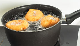 烹调在水壶的煮沸的油的油炸圈饼 免版税库存照片