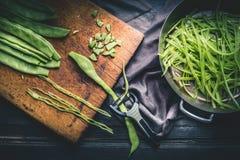 烹调在黑暗的土气厨房用桌背景的青豆准备 免版税图库摄影