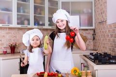 烹调在从未加工的新鲜蔬菜的厨房的两个愉快的女孩 免版税库存图片