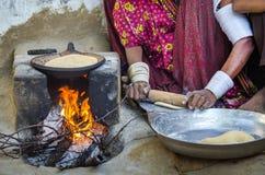 烹调在柴火的妇女食物 免版税库存图片