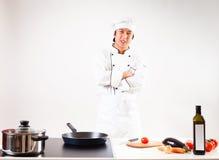 烹调在他的厨房里的厨师 免版税库存照片