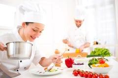 烹调在他的厨房里的年轻可爱的专业厨师 免版税图库摄影
