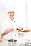 烹调在他的厨房里的年轻可爱的专业厨师 图库摄影