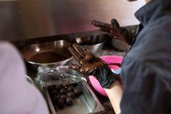烹调块菌状巧克力的题材 特写镜头手年轻白种人妇女和人厨师有纹身花刺的和制服的准备,做 库存图片