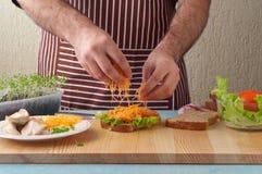 烹调大三明治的人在家庭厨房里 图库摄影