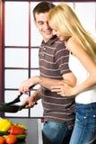 烹调夫妇愉快的年轻人 免版税图库摄影