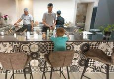 烹调孩子的厨师和厨师食物在都市餐馆露天场所厨房  库存图片