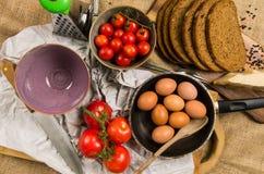 烹调定期的平底锅用鸡蛋、切的黑麦面包、两个碗、蕃茄和刀子在帆布 免版税库存图片