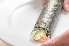烹调寿司卷用米,三文鱼的手和 免版税库存照片
