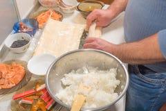 烹调寿司用米、三文鱼和nori的手 免版税图库摄影