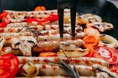 烹调开胃烤香肠和菜的过程  免版税库存图片