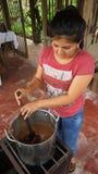 烹调恶豆的年轻拉丁妇女在一个小气体厨房里 热化可可子是过程的部分做的手工制造cho 库存图片