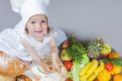 烹调想法 厨师制服的白种人小女孩 免版税库存图片