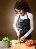 烹调愉快的妇女 健康食物-新鲜的黄瓜 库存照片