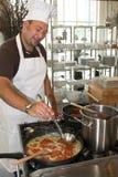 烹调意大利意大利面食的主厨 免版税图库摄影
