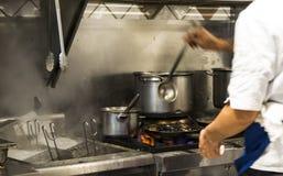 烹调意大利食物的苦干者国际厨师在一家国际餐馆 免版税图库摄影