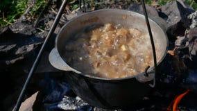 烹调户外在铸铁大锅 烹调在火 在一口大锅的食物在火 股票录像