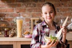 烹调技能女孩准备的沙拉晚餐的孩子 免版税库存照片