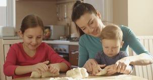 烹调揉的面团的女儿和儿子帮助的母亲在一起花费时间的厨房和家庭里 股票视频