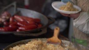烹调放被炖的金黄圆白菜在猪肉香肠旁边入服装的塑料板材 街道食物在城市市场的待售 影视素材