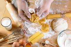 烹调新意大利未煮过的自创面团tagliatelle在木桌上,在厨师的手上,设置了 库存图片