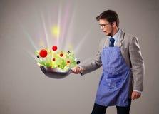 烹调新鲜蔬菜的年轻人 免版税库存图片